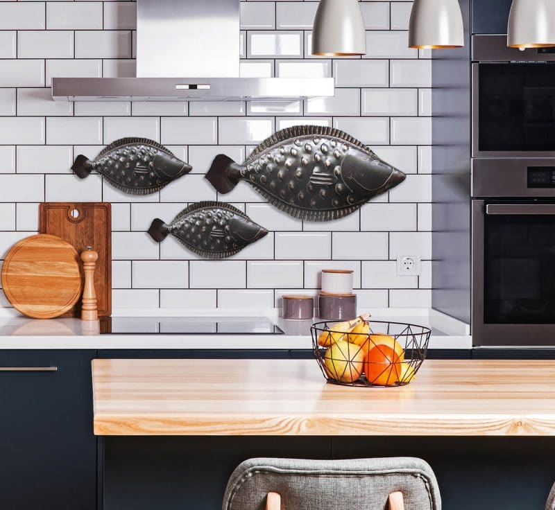 Chase Allen's handcrafted flounder sculptures against subway tiles in coastal kitchen